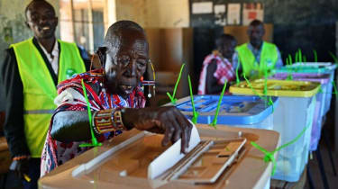 An elederly Maasai woman is watched over by an IEBC official as she casts her vote in Ilngarooj, Kajiado County, Maasailand, on March 4, 2013 during the nationwide elections. Long lines of Ke