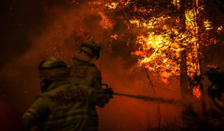 SYDNEY, AUSTRALIA - DECEMBER 19: Fire and Rescue personal use a hose as they try to extinguish a bushfire as it burns near homes on the outskirts of the town of Bilpin on December 19, 2019 in