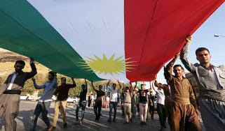 Iraqi Kurds campaigning for independence carry their flag through the streets