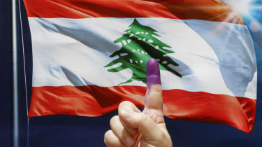 An ink-stained index finger before a poster depicting a waving Lebanese flag