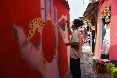 A man looks on as an artist paints a wall of a slum hutment at the Asalpha village in Mumbai on December 17, 2017. With an aim to alter the perspective the world has of urban slums city artis