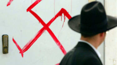 PETAH TIKVA, ISRAEL - MARCH 5:(ISRAEL OUT)A Jewish man looks at anti-semitic graffiti which was sprayed on the gate of a synagogue March 5, 2006 in Petah Tikva, near Tel Aviv, in central Isra