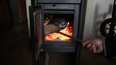A man adds firewood into a wood burning stove in Temuco, about 680 km south of Santiago, Chile on June 22, 2019. - The indiscriminate use of firewood to heat up and combat the cold of the sou