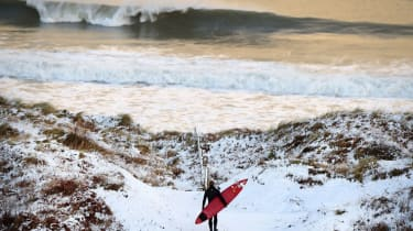 ANTRIM, NORTHERN IRELAND - JANUARY 14:Pro surfer Alastair Mennie makes his way towards the beach at Portrush on January 14, 2015 in Antrim, Northern Ireland. The province experienced heavy sn