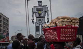 A man walks by with a basket of bread during the official presentation ceremony of three new human-like robots