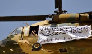 A helicopter flying a Taliban flag above Kandahar