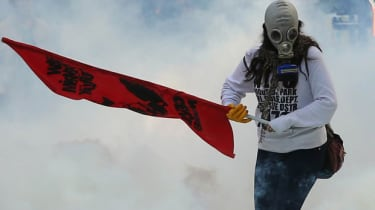 A person holds a flag as Turkish police uses tear gas and water cannon