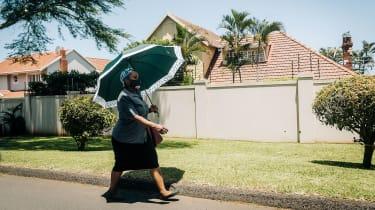 A South African woman walks through Durban wearing a mask