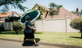 A South African woman walks through Durban wearing a mask