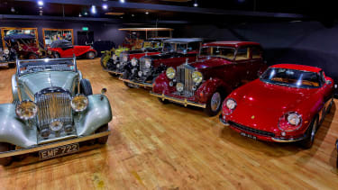 Vintage cars parked on the wooden floor of a hall