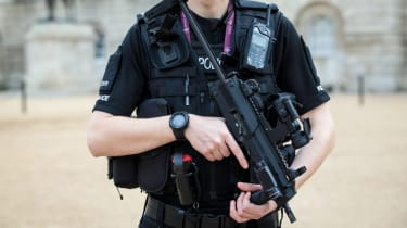 An armed police officer patrols in Horse Guards Parade in London