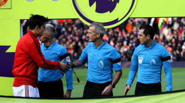 Manchester United captain Harry Maguire shakes hands with referee Martin Atkinson before a Premier League match