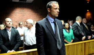 South African Olympic sprinter Oscar Pistorius (C) appears on February 19, 2013 at the Magistrate Court in Pretoria as he father Henke (3rd L), brother Carl (2nd L) and sister Aimee (L) atten