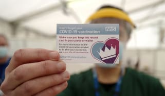 Man shows NHS vaccine card