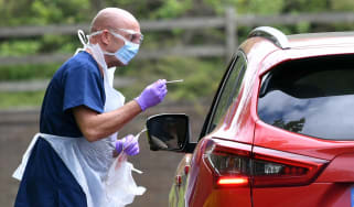 An NHS nurse carries out a Covid test at a drive-through testing centre.