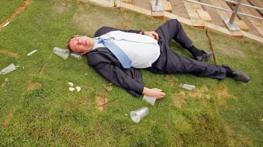 ASCOT, UNITED KINGDOM - JUNE 20:A man lies on the ground as race-goers walk past him on the first day of Royal Ascot, at the Ascot Racecourse on June 20, 2006 in Ascot, England.The event has