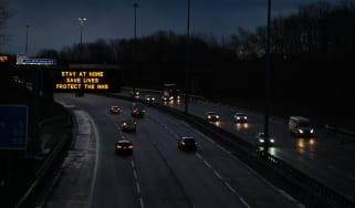 Traffic on the M8 motorway passes a road sign advising motorists to stay at home