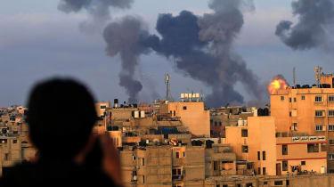 A Palestinian boy watches as Israeli airstrikes hit the southern Gaza region of Khan Yunis