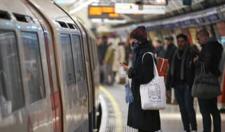 A woman wearing a face mask waits on the platform for the London Underground