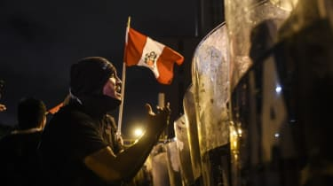 Demonstrators confront riot police during a protest against interim President Manuel Merino
