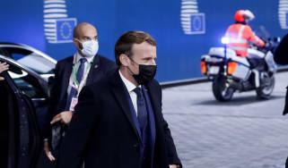 Emmanuel Macron arrives at the European Parliament building wearing a black face mask.