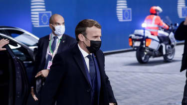 Emmanuel Macron arrives at the European Parliament building wearing a black face mask.