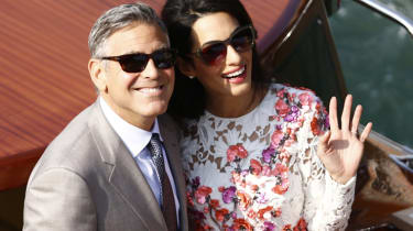 US actor George Clooney and his wife Amal Alamuddin stand on a taxi boat on the Grand Canal on September 28, 2014 in Venice. Hollywood heartthrob George Clooney and Lebanese-British lawyer Am