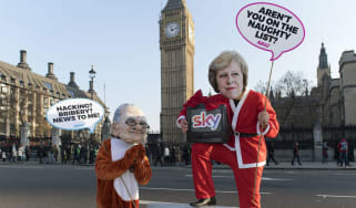 rotesters dressed as Rupert Murdoch oppose the Sky takeover outside Parliament