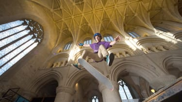 MALMESBURY, ENGLAND - FEBRUARY 18:A skateboarder jumps from a ramp that has been erected inside the 12th century former Benedictine Malmesbury Abbey on February 18, 2015 in Malmesbury, Englan