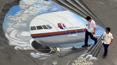 Students walk past a giant mural featuring missing Malaysia Airlines flight MH370 displayed on the grounds of their school in Manila's financial district of Makati on March 18, 2014, created