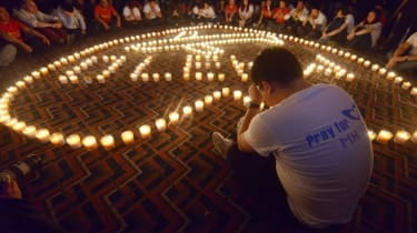 A Chinese relative (R) of passengers on Malaysia Airlines flight MH370 prays in front of candles as he takes part in a prayer service at the Metro Park Hotel in Beijing on April 8, 2014. The