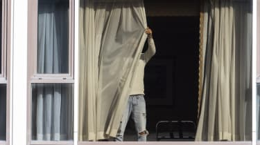 A man draws his curtains at the Radisson Blu hotel after arriving at Heathrow