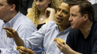 US President Barack Obama (C) talks with British Prime Minister David Cameron (R) as they eat hot dogs while sitting in the stands at University of Dayton Arena in Dayton, Ohio, March 13, 201