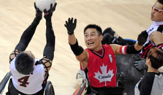 Canada's Ian Chan (R) vies for the ball with Japan's Shinichi Shimakawa (L) in their mixed wheelchair rugby game at the 2008 Beijing Paralympic Games on September 12, 2008 at the USTB Gymnasi