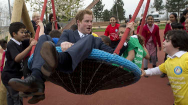 LONDON, ENGLAND - APRIL 04:HRH Prince Harry explores a new playground with a group of children from Gainsborough Primary school in Newham during an official visit to Queen Elizabeth Olympic P