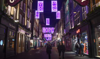 Christmas lights hang over an otherwise quiet Carnaby Street in London