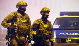 Police stand guard after the attack at a Munich shopping centre