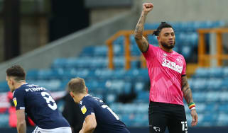 Colin Kazim-Richards of Derby County raises his right fist as other players take the knee ahead of the match against Milwall