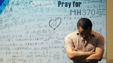 A victim's relative stands in front of tributes to flight MH370