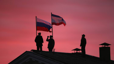 BAKHCHYSARAI, UKRAINE - MARCH 17:Cossack men install a Russian flag and a Crimean flag on the roof of the City Hall building on March 17, 2014 in Bakhchysarai, Ukraine. People in Crimea overw