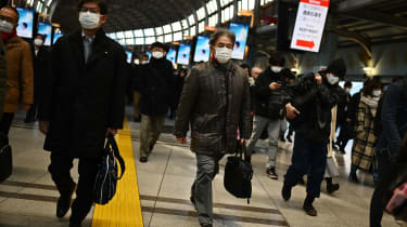 Mask-clad commuters make their way to work during morning rush hour at the Shinagawa train station in Tokyo on February 28, 2020. - Tokyo's key Nikkei index plunged nearly three percent at th