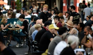 People sit outside at restaurants in Soho, London.
