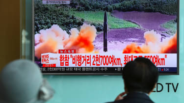 People watch news screen showing North Korean missile launch