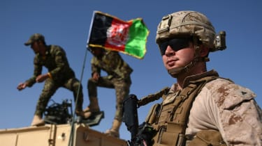 A US Marine looks on as Afghan National Army soldiers raise the Afghan National flag
