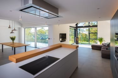 Contemporary kitchen opening into a living area behind