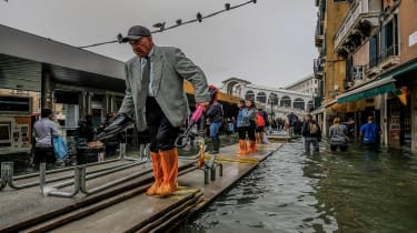 """VENICE, ITALY - OCTOBER 29: People walk across temporary walkways following flooding caused by a high tide on October 29, 2018 in Venice, Italy. Due to the exceptional level of the """"acqua alt"""