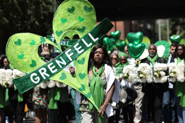 LONDON, ENGLAND - JUNE 14:People hold tributes as they walk to the Wall of Truth to mark the one year anniversary of the Grenfell Tower fire on June 14, 2018 in London, England. In one of Bri