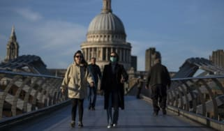 Pedestrians walk across the Millennium Bridge in front of St Pauls Cathedral.