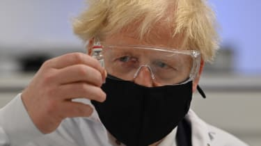 Boris Johnson with a vial of the Oxford-AstraZeneca vaccine