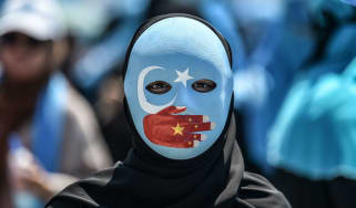 A demonstrator wears a mask showing solidarity with China's Uighur population.